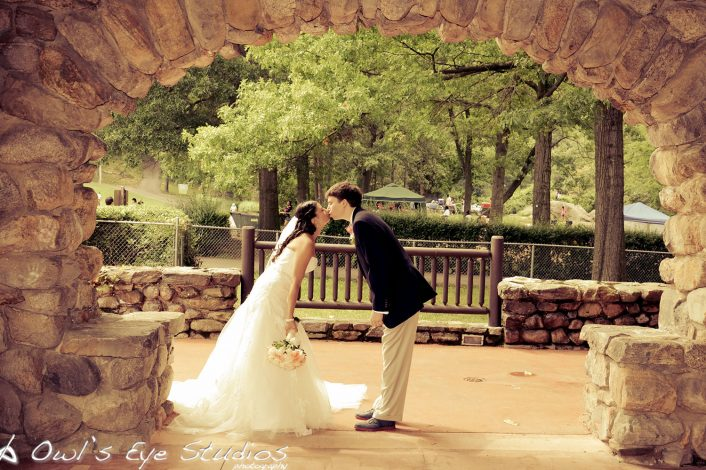 a newly married couple leaning in to kiss under a stone arch