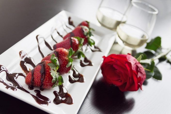 Chocolate Covered Strawberries and Wine sitting on a white plate