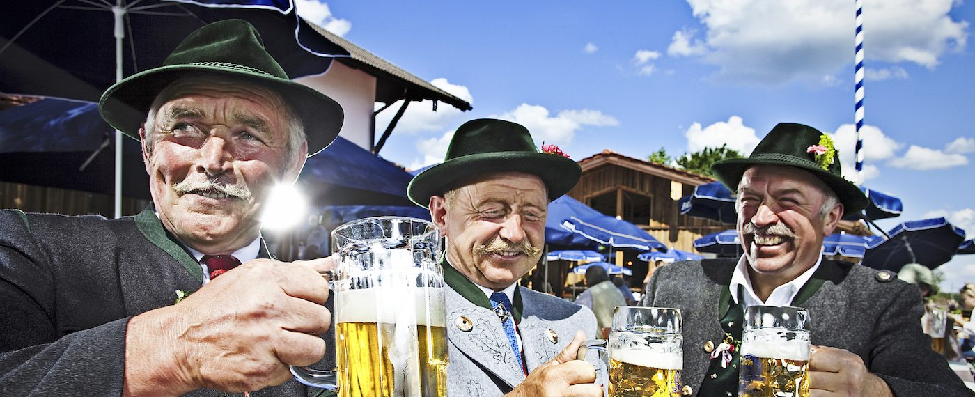 Three Bavarians in Traditional Clothing Drinking Beer and Celebrating in a Beergarden.