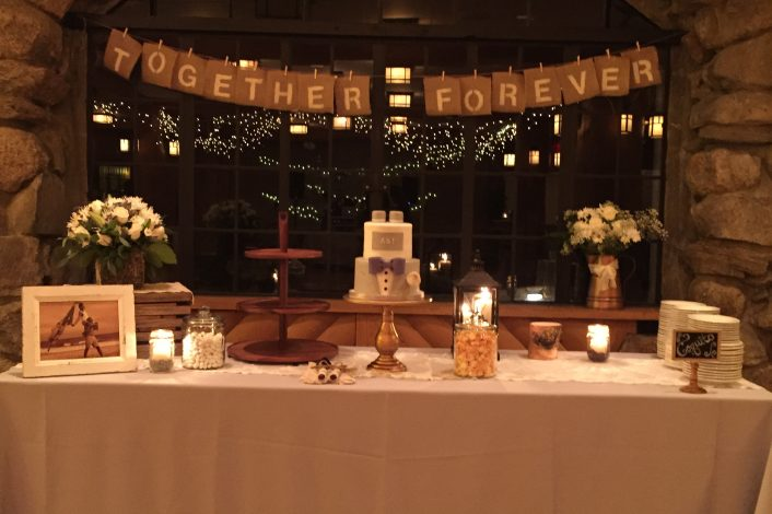 A wedding cake, plates, and an image of the newlywed couple sitting on a long rectangular table