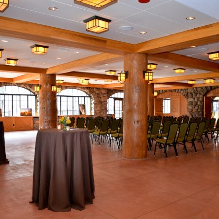 A large room arranged with chairs for an event and bar height, circular tables