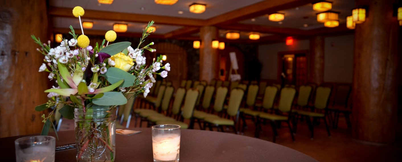 Large room with chairs aligned in rows. A vase of flowers and two candles sit in the foreground on a table