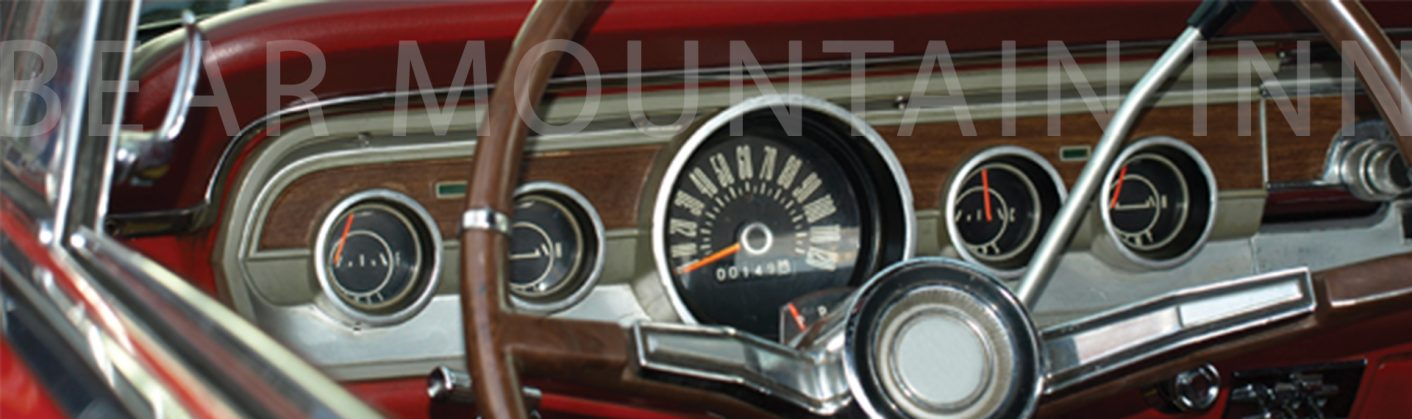 Dashboard of an old car showing the steering wheel, speedometer, and other gauges