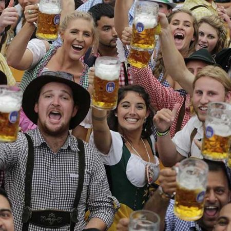 People dressed in Bavarian attire are toasting the camera