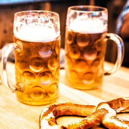 Two mugs of beer sitting next to a giant pretzel