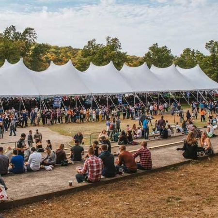 An event with a giant tent and lots of people sitting and standing around with beers in their hands